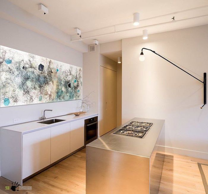 abstract art backsplash, metal kitchen island, kitchen island with stove, wooden floor, white cabinets