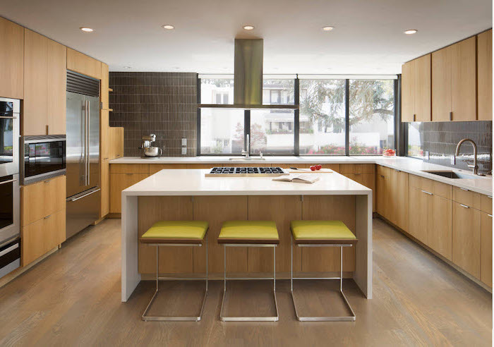 green bar stools, wooden cabinets, white countertops, kitchen island with stove, grey tiled backsplash