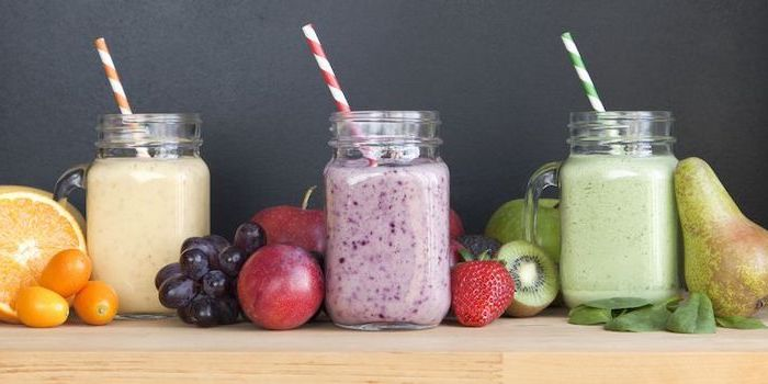healthy smoothie recipes, jars filled with different smoothies, orange and cherry tomatoes, different fruits