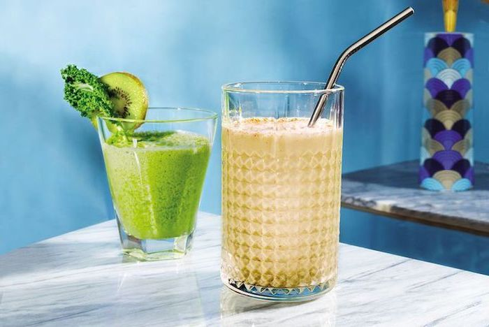 marble countertop, two glasses on top, silver straw, protein smoothie recipes, kiwi slice on the rim