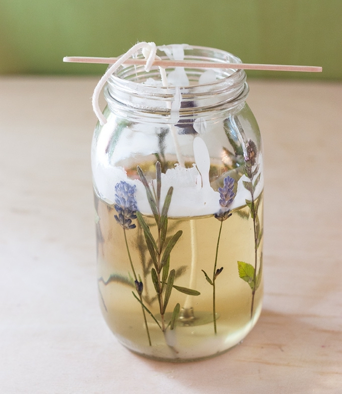 large jar, filled with candle wax, diy candles, candle wick, held on top with a wooden stick