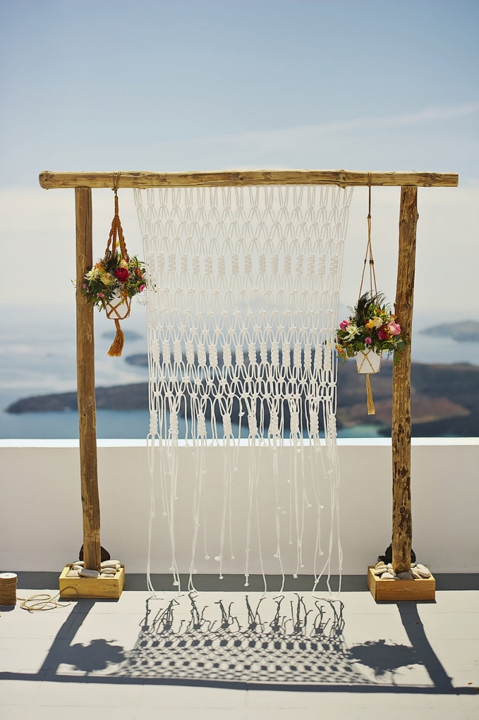 large wooden arch, plant hangers, flower bouquets, macrame hanging, blue sky and ocean
