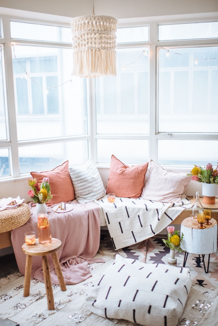 pink and white throw pillows, how to macrame, pink blanket, small wooden tables, large windows