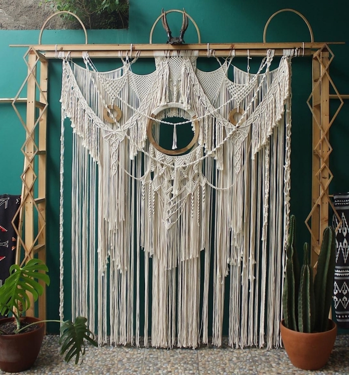large wooden arch, macrame hanging, white macrame curtain, potted plant and cactus
