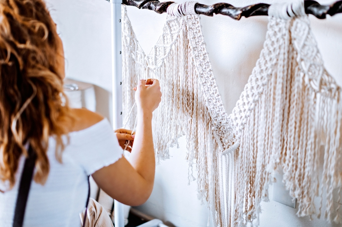 woman knotting, macrame patterns, wearing a white top, white wall