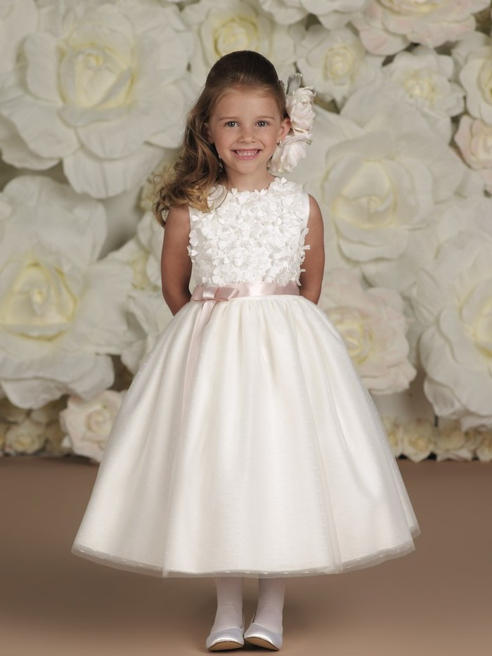 white roses background, white lace and tulle dress, white shoes, flower girl hair, brown wavy hair