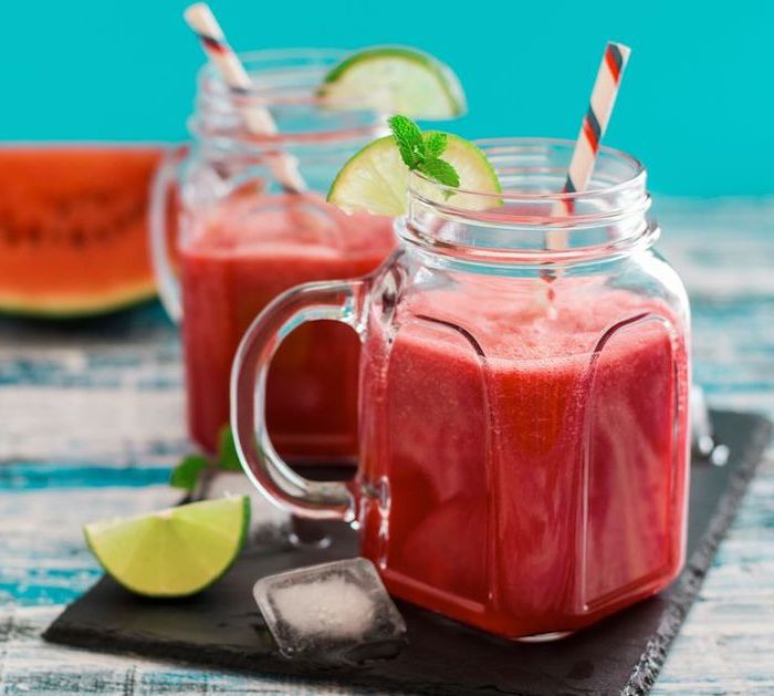 how to make a smoothie with frozen fruit, two jars, lime slices on the rim, ice cubes