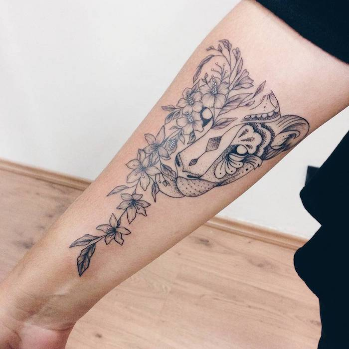 feminine tattoos, lion head and flowers, forearm tattoo, wooden floor