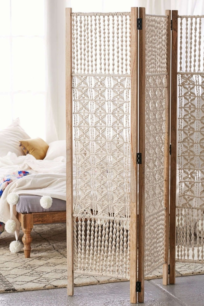 wooden room divider with macrame, macrame hanging, cement floor, white wall, wooden bed frame