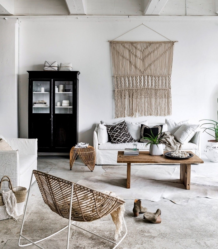 white sofa, macrame wall art, black cabinet, wooden table, cement floor, wooden armchair
