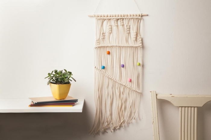 wooden chair, hanging white wooden shelf, potted succulent, macrame wall art, white wall