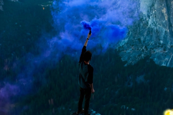 man holding a blue bomb, standing on top of a rock, background tumblr, mountain landscape