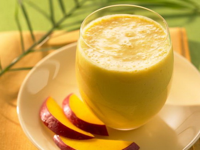 mango slices and glass, on a white plate, how to make a smoothie with frozen fruit