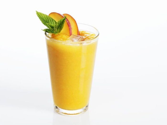 tall glass, how to make a smoothie with frozen fruit, mango slices on the rim, mint on top
