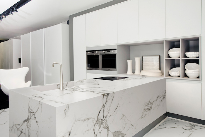 marble kitchen island and floor, white cabinets, open shelving, white armchair, kitchen island countertop