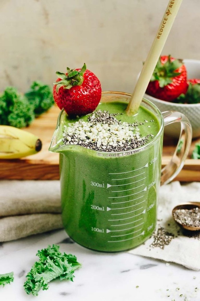 green smoothie, in a measuring cup, smoothie recipes with frozen fruit, strawberry on the rim