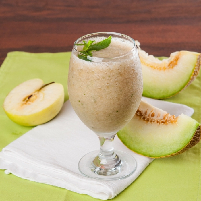 smoothie recipes with frozen fruit, sliced melon and apple, tall glass, on a white cloth, mint on top