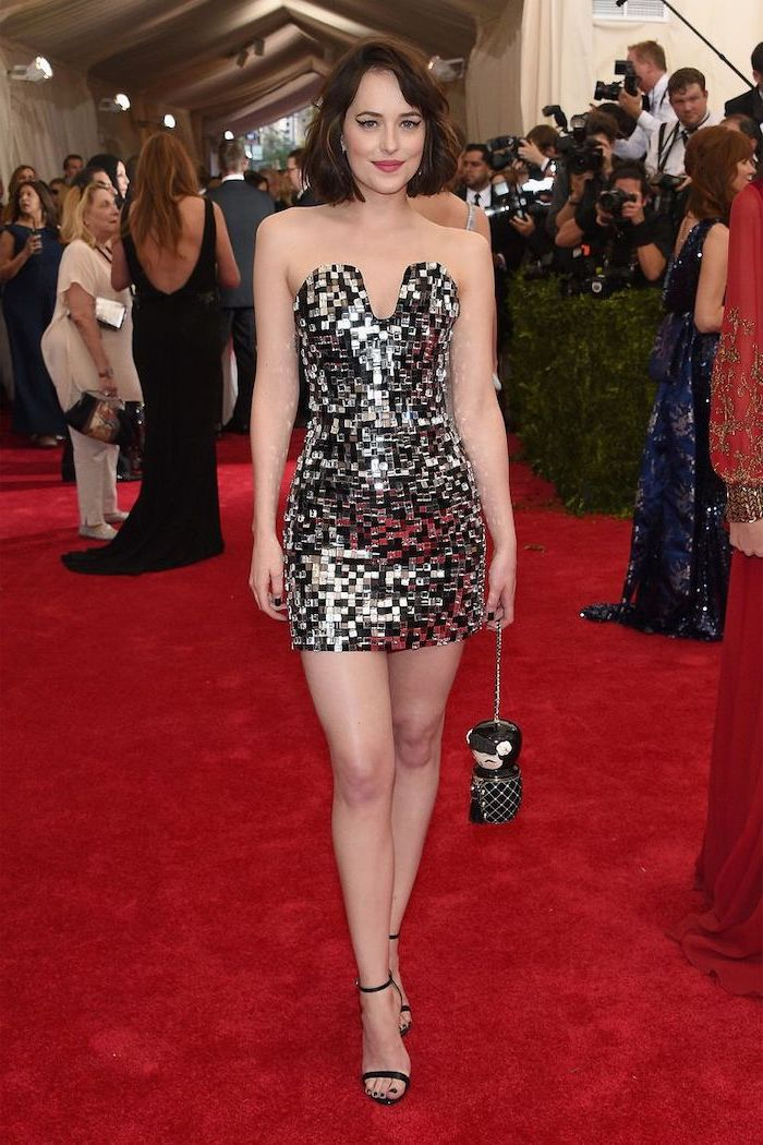 dakota johnson, wearing a short dress, with black and silver sequins, strapless dress, met gala theme