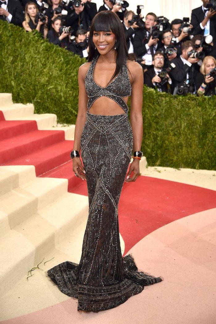 dark grey long dress, naomi campbell, met gala red carpet, black hair with bangs