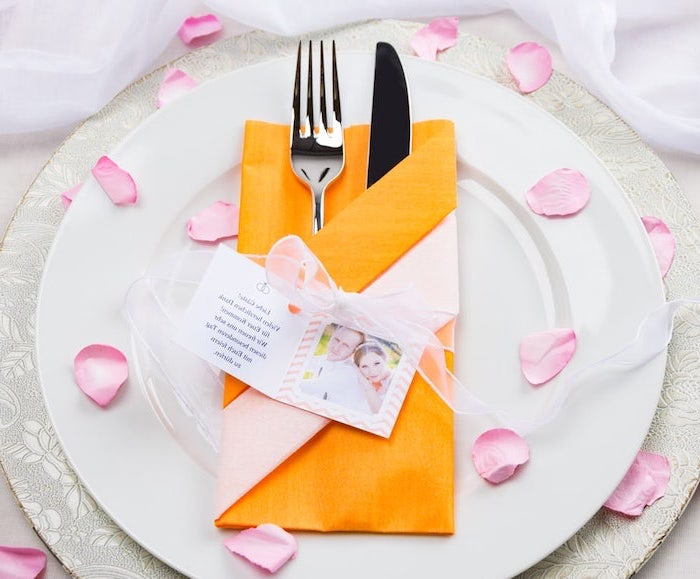 how to fold cloth napkins, orange napkin, silverware inside, on white plates, rose petals scattered around