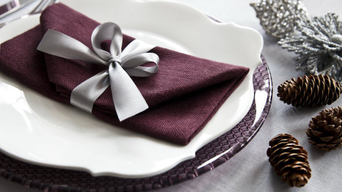 purple napkin, folded as an envelope, grey ribbon around it, how to fold napkins, white and purple plates