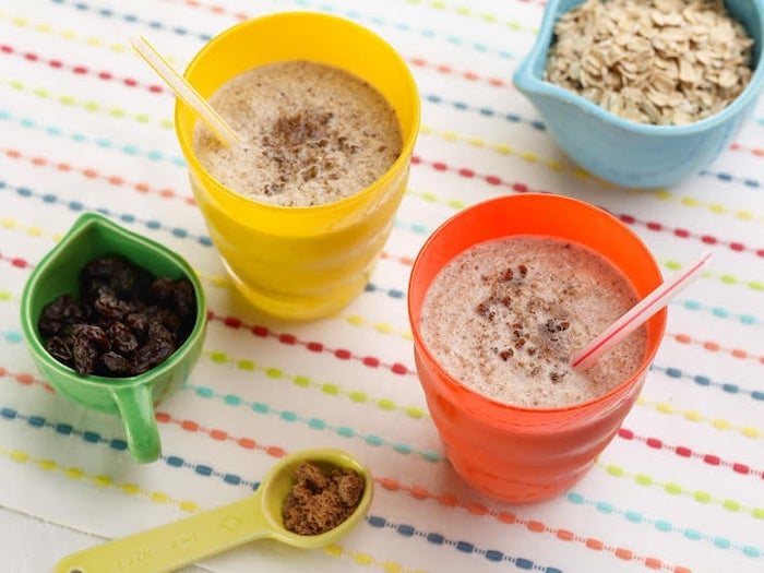 oatmeal in a blue bowl, orange and yellow glasses, how to make a mango smoothie, colourful cloth