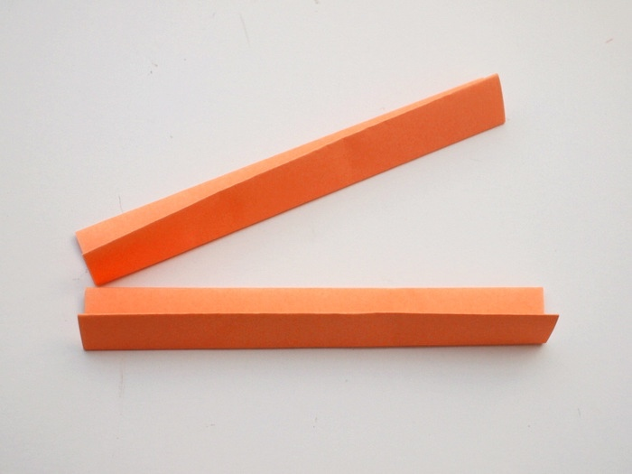 orange paper, folded in two, on a white background, dun indoor games for kids, step by step, diy tutorial