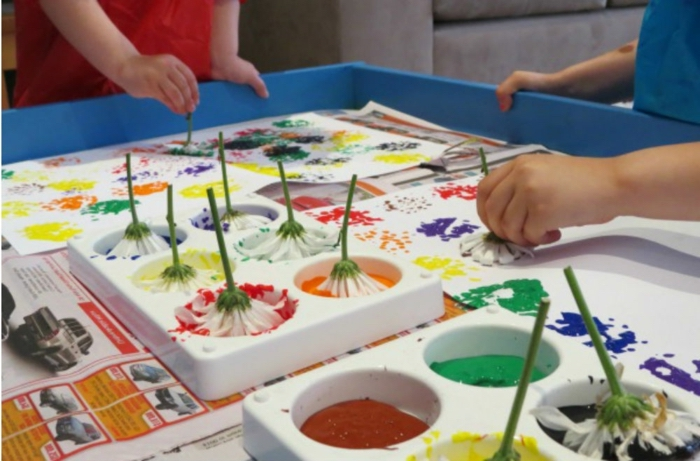 children painting with flowers, hands on activities, orange and red, yellow and purple paint