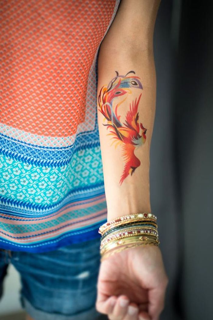 watercolour phoenix, with spread wings, forearm tattoo, leg tattoos for girls, colourful top, denim shorts