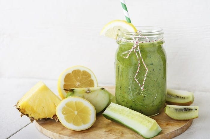 sliced cucumber and kiwi, apple and pineapple, how to make healthy smoothies, wooden cutting board
