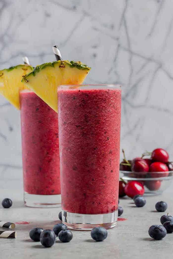 tall glasses, pineapple slices on the rim, how to make healthy smoothies, blackberries around, cherries in a bowl