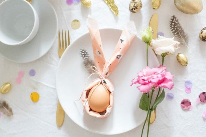 bunny shaped napkin, egg inside it, on a white plate, how to fold cloth napkins, pink and white flowers