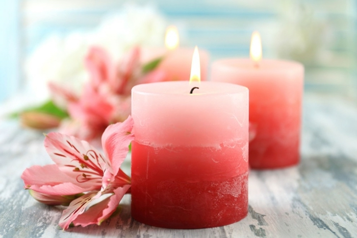 diy candles, small round candles, in shades of pink, pink flowers around them, on a wooden table
