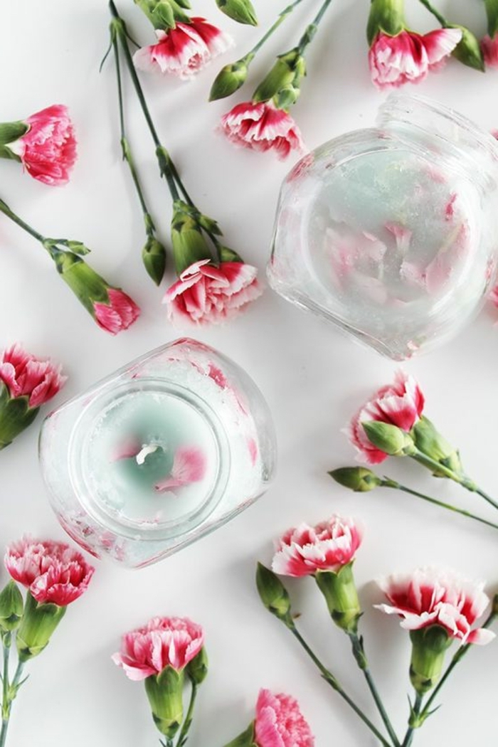 pink cloves, scattered on a white countertop, mason jar candles, cloves petals inside the candle wax