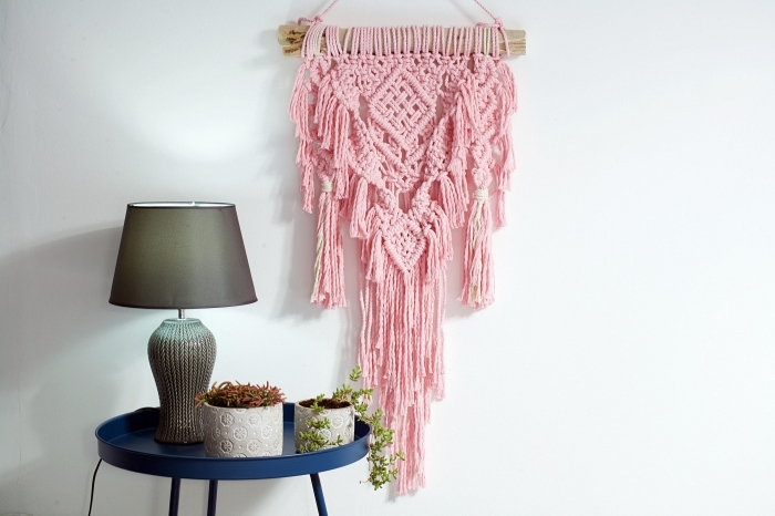 pink wall decoration, blue metal table, potted plants, white wall, how to do macrame