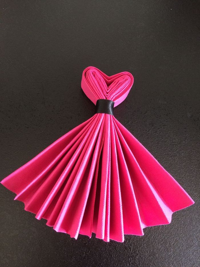 pink napkin, folded in the shape of a dress, tied with a black ribbon, how to fold cloth napkins