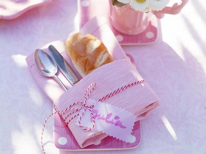 pink napkin, silverware and bread inside, red and white ribbon around it, name tag, how to fold napkins