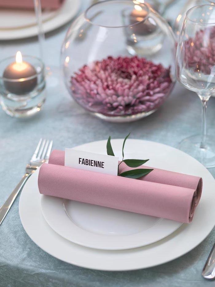 white plates, pink napkins, folded as scrolls on top, napkin folding ideas, glass vases around