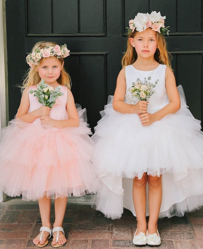 two girls, one with white tulle dress, the other with pink tulle, little girl dresses, white sandals, flower crowns