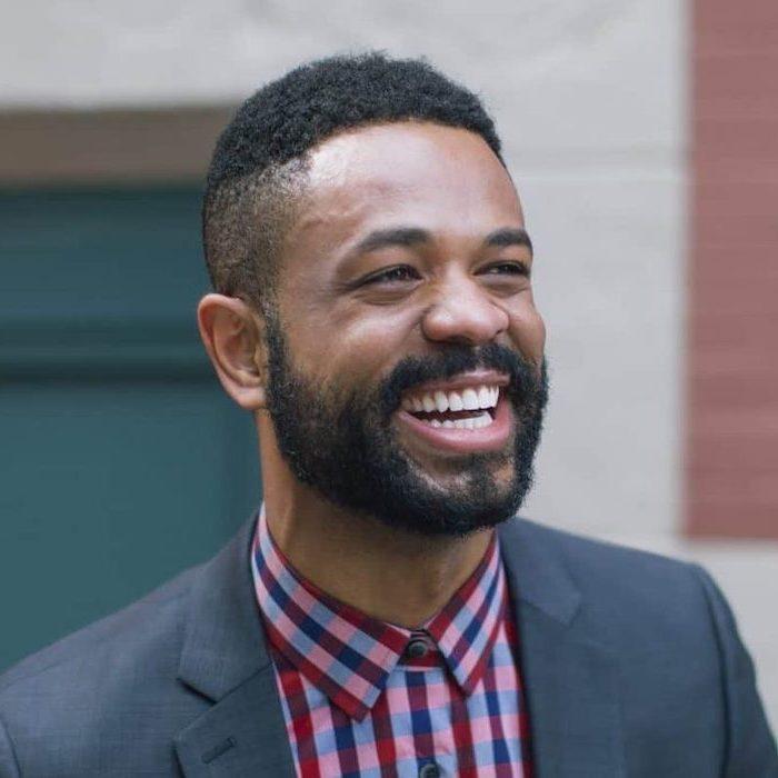 plaid shirt, man smiling, grey jacket, medium haircuts for men, black curly hair, black beard