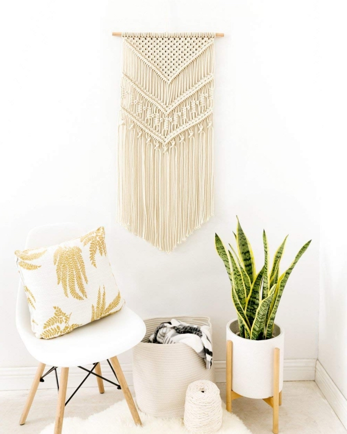 white chair, gold and white throw pillow, macrame wall hanging patterns, white wall, potted plant