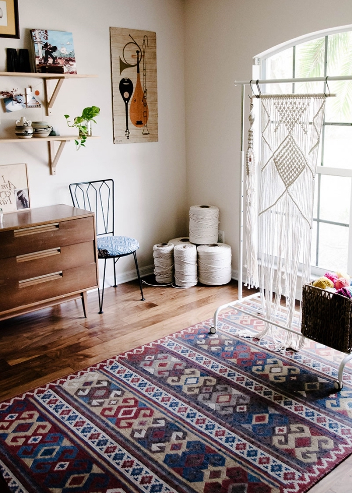 printed rug, woven wall tapestry, hanging shelves, wooden drawers, large window, hanging art, wooden floor