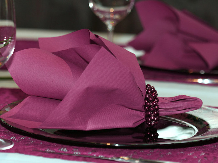 purple paper napkin, purple pearl ring around it, on a purple plate, napkin folding ideas