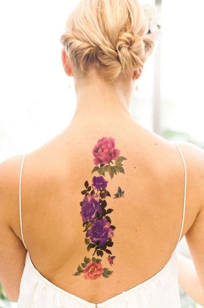 blonde hair, pink and purple flowers, back tattoos, small tattoos with meaning, white top