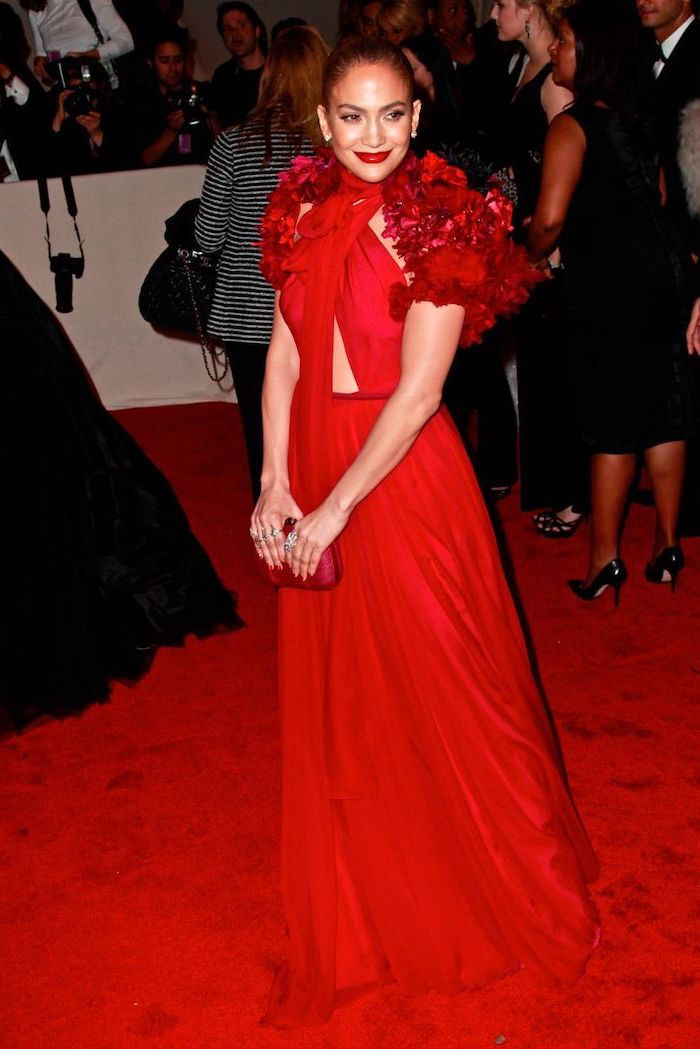 long red dress, jennifer lopez, on the red carpet, costume institute, red clutch bag, brown hair, in a low updo