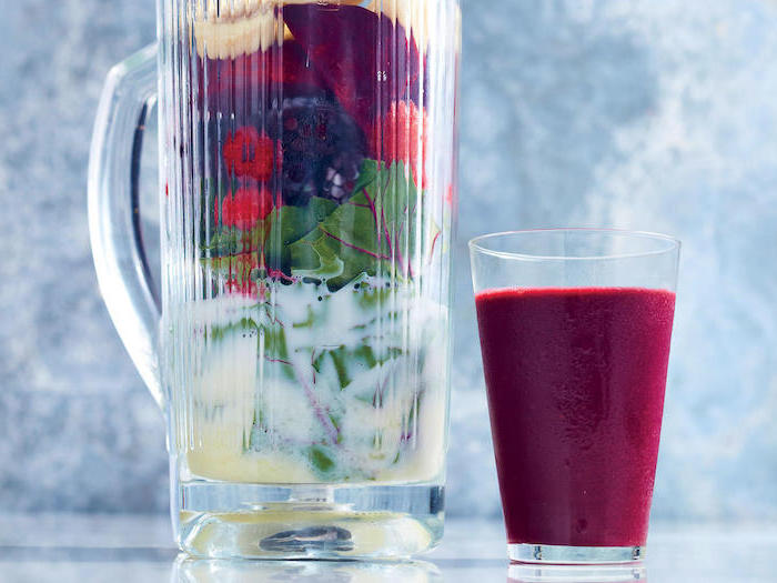 large pitcher, filled with fruits and milk, tall glass next to it, how do you make a smoothie