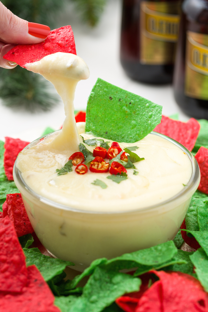 red and green tortilla chips, veggie appetizers, sour cream in a glass bowl