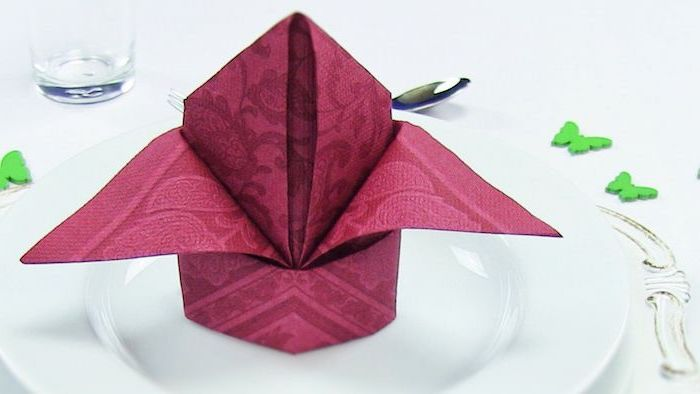 red folded napkin, on a white plate, how to fold dinner napkins, green butterflies around