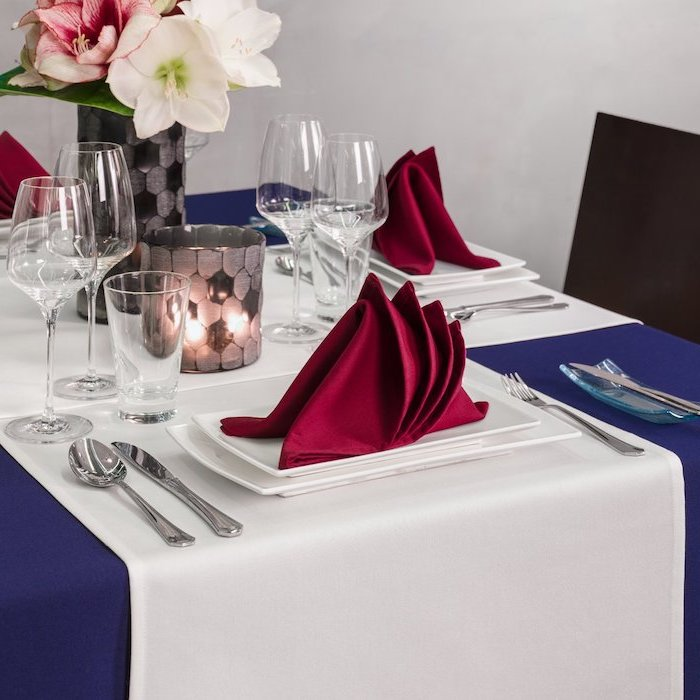 flower bouquet, how to fold dinner napkins, red folded napkins, on white plates, blue table cloth