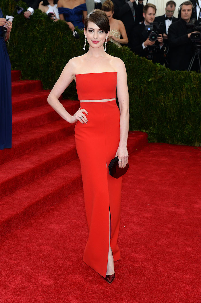 met gala fashion, anne hathaway, red top, red long skirt, short brown hair, dark red heels, clutch bag